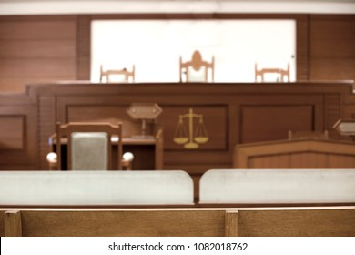 empty courtroom interior attester talking to magistrate in legal concept. focus on wood chair.