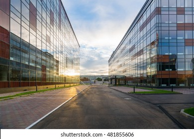 Empty courtyard of a modern office center, a new glass commerce building, empty parking lots, sun flares