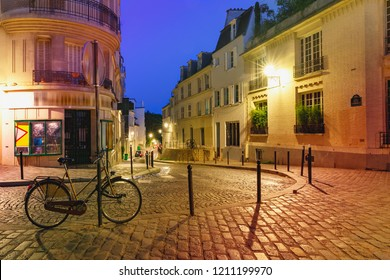 Empty cozy street with bike and street lamp at night, quarter Montmartre in Paris, France
