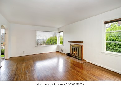 Empty craftsman style living room interior with fireplace and polished hardwood floor.
