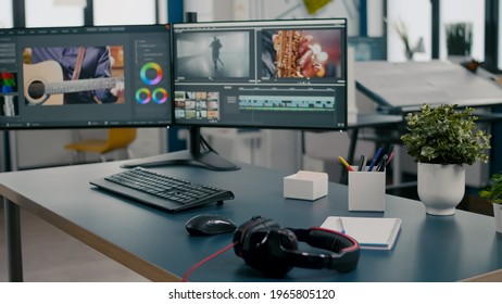 Empty creative multimedia studio with professional computer placed on desk, dual monitor setup. Video editing start up company agency with no people in it and post production software on pc displays