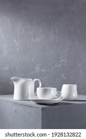 Empty crockery or ceramic dishes set. Kitchen dishware and tableware on grey surface near wall background texture