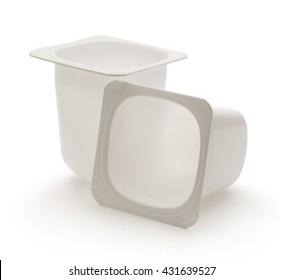 Empty crushed plastic yogurt pots on white
