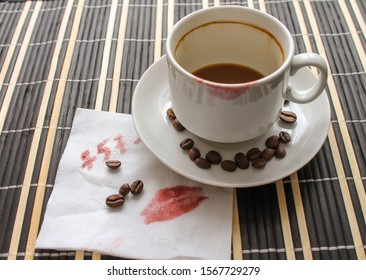 Empty cup of coffee with lipstick prints of a woman. Kiss the track on a napkin with a phone number.