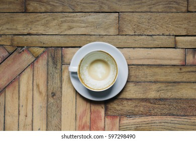 Empty cup of coffee on wooden table background. top view