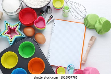 Empty cupcake cases with different kitchen utensils on wooden table