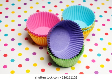 empty cupcake cases on a colorful dotted background