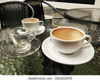 Empty cups of coffee and tea on ground glass table and black chairs
