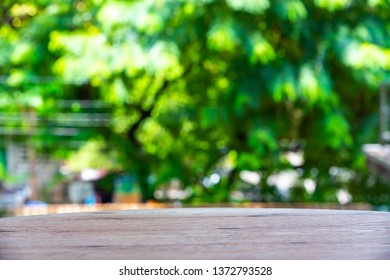 Empty curved wooden table texture, Green garden blurred bokeh background, Selective focus