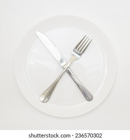Empty cutlery isolated on white background/ White shiny plate with folk and knife