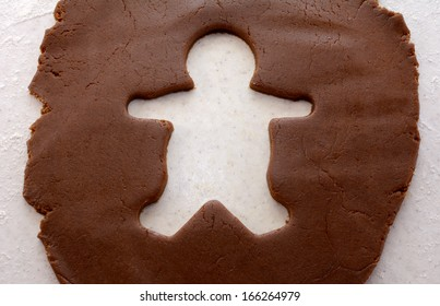 Empty cutout shape of a gingerbread man in biscuit dough
