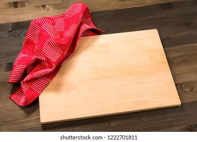 Empty cutting board and red cloth on wooden surface