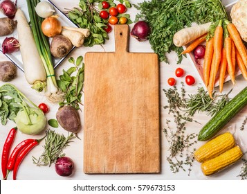 Empty cutting board and various raw vegetables for  tasty and healthy  cooking, top view, place for text, frame. Vegan or vegetarian food concept