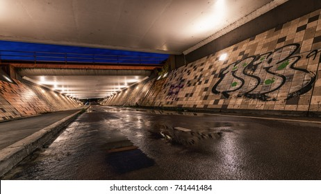 Empty and dark biker viaduct with grafiti and water puddles at the beginning of the evening