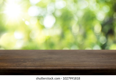 Empty dark brown hard wood table top with sun and blur green tree bokeh background, Template mock up for montage of product.