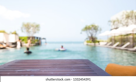 Empty dark wood table with blur people relaxing and enjoy a luxury infinity swimming pool in the beach hotel. Background usage or present your product can be used as mock up or copy space for product