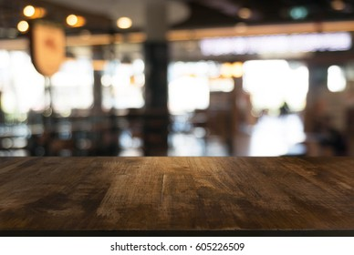 Empty dark wood table top and blur of resturant lights background/selective focus .For montage product display