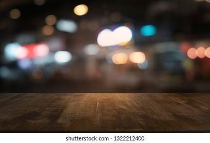 Leer dunkler Holztisch vor abstraktem, unscharfem Bokeh-Hintergrund des Restaurants . kann zur Anzeige oder Montage Ihrer Produkte verwendet werden.Für den Weltraum aufrüsten