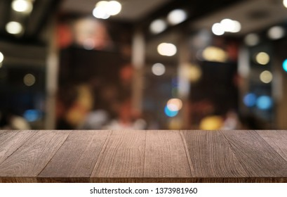 Empty dark wooden table in front of abstract blurred bokeh background of restaurant . can be used for display or montage your products.Mock up for space