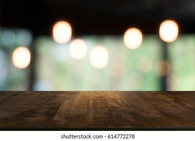 Empty dark wooden table in front of abstract blurred background of restaurant . can be used for display or montage your products.Mock up for display of product