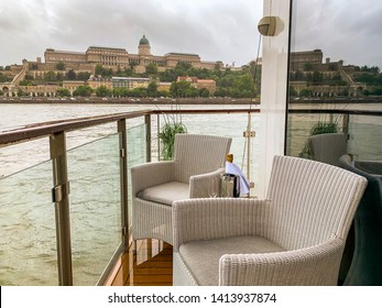 Empty deck chairs with bottle of champagne on balcony of luxury riverboat cruise ship along banks of Danube River in Budapest, Hungary.