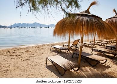 Empty deck chairs and umbrellas on the beach in Port de Pollenca, Majorca