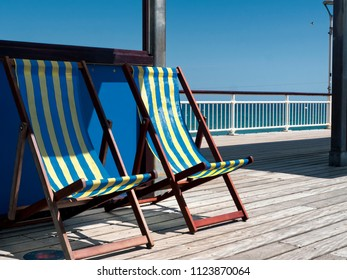 Empty deckchairs on pier