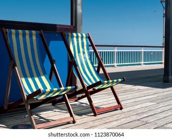 Empty deckchairs on pier