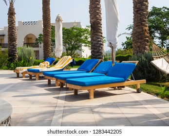 Empty deckchairs with towels at the resort, relaxation and vacation concept