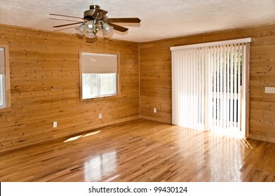 An empty den or living area in a house with pine walls,oak flooring and vertical blinds.