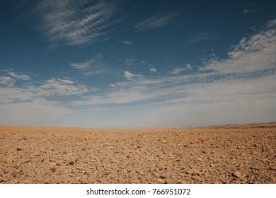 Empty desert area horizon line. Dry ground with blue cloudy sky over the sand.