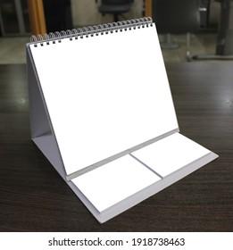 Empty Desk Calendar on wood table. Templates Mockup design concept