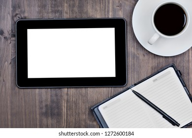 Empty digital tablet with notebook and coffee cup on desk