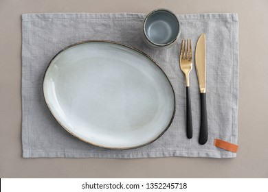 Empty dinner table place setting with grey ceramics and gold and black cutlery