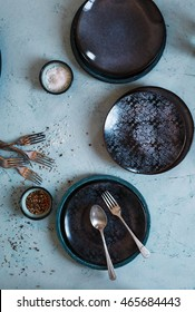 Empty dinning black decorative green three bowls over turquoise stone table with cutlery complements and salt peppers bowls. Rustic old styling. Top view.