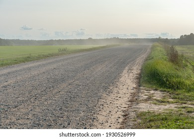 An empty dirt road in the middle of an empty field and forest. The wind blows dust and sand across the field on a dry summer day.
