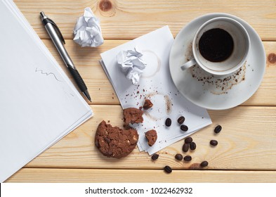 Empty dirty coffee cup with cookies and pen, sheet and crumpled paper on the wooden table. Top view. Conceptual photo