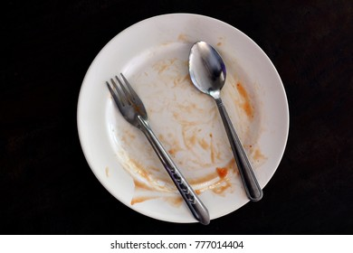 empty and dirty dish after eating food, plate fork and spoon