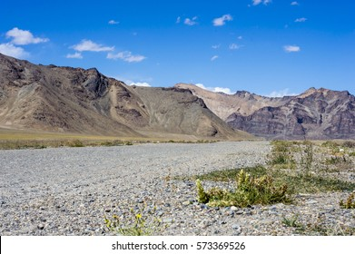 Empty dirty off road in Pamir Mountains in Gorno-Badakhshan Autonomous Region, Tajikistan