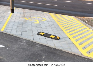 Empty disable parking lot or space with wheelchair symbol or sign on the urban street in the city with tire barrier to protect car to drive over on sidewalk