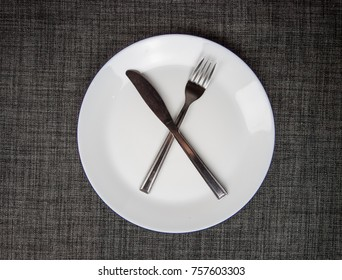 Empty dish, knife and fork on table