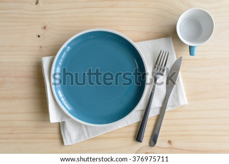 Empty dish with knife and fork on old wooden background, Top view