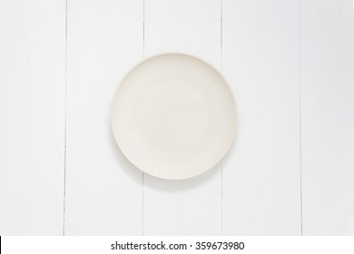 Empty dish on wooden white table, Top view