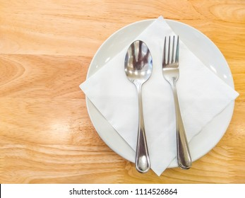 Empty dish with spoon and fork on wood table.