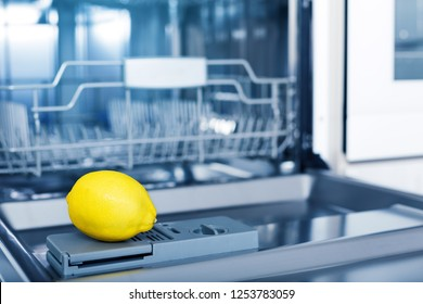 Empty dishwasher with fresh yellow lemon on shelf, aroma freshness care concept, clean equipment,  home appliance dishwashing machine in kitchen interior, no people