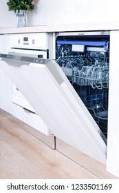 Empty dishwasher with opened door, home appliance dishwashing machine in kitchen interior, no people