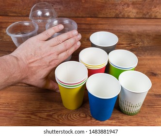 Empty disposable paper cups and hand pushing back plastic cups as concept of renounce to use plastic disposable tableware