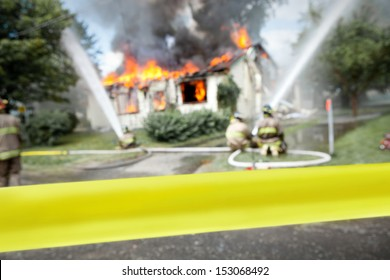 """Empty """"do not cross"""" tape with firefighters and a burning house in the background"""