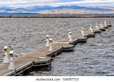 An empty dock projects outward into the waters of Lake Champlain in Burlington, Vermont.