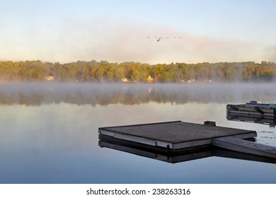 Empty docks at Bear Lake, Noelville, Ontario, await cottagers awakening to fish and swim as the sun rises, geese swoop past over heard and the misty nighttime fog begins to lift.